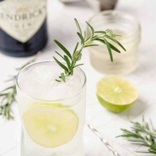 Rosemary gin and tonic cocktail garnished with lime and a rosemary sprig.