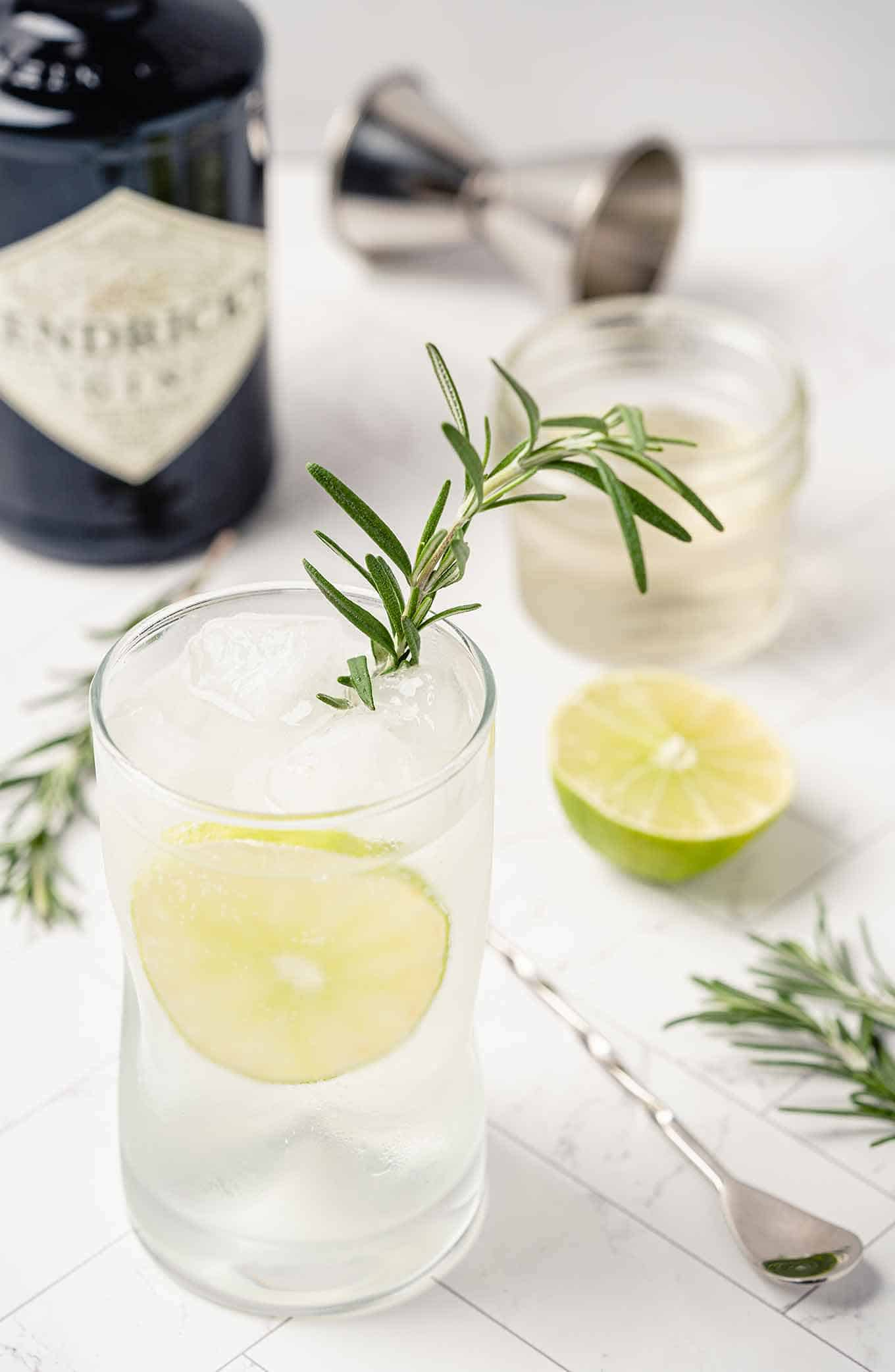 Rosemary gin and tonic garnished with lime and fresh rosemary, extra ingredients in the background.
