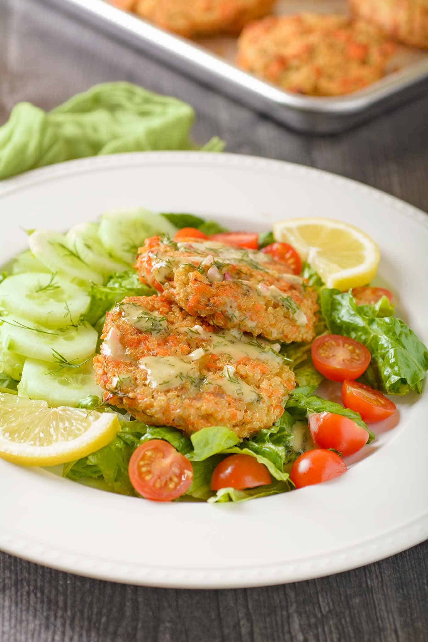 A serving of baked salmon quinoa cakes with salad, creamy lemon and dill dressing, and a sheet pan with more salmon patties in the background.