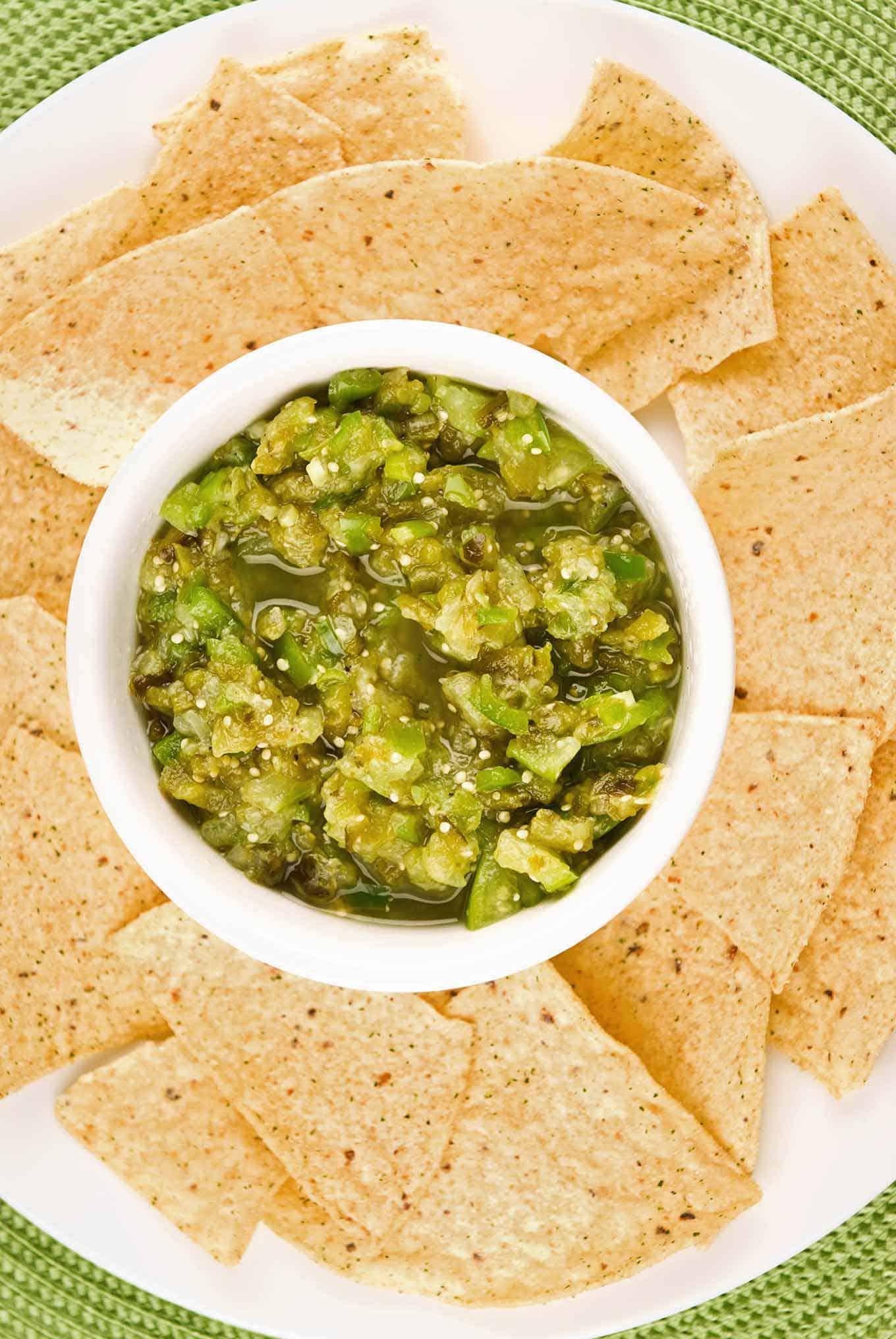 A platter of tortilla chips arranged around a bowl of salsa verde.