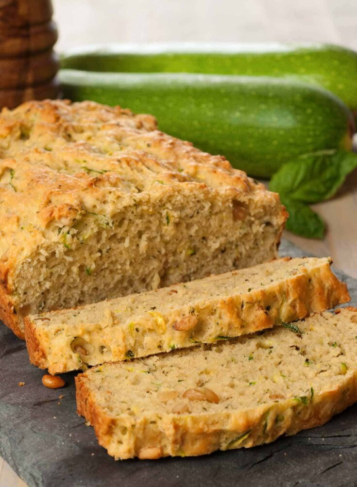 Flavored with basil pesto and Parmesan cheese, this savory zucchini bread is easy to make and a refreshing change from the sweet variety. #zucchinibread #quickbread