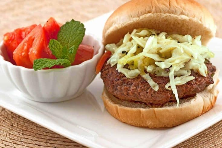 These uniquely flavored burgers topped with crisp sesame slaw are full of Asian-style flavors including scallions and ginger. #asianburgers #hamburgers #burgers #scallionburgers