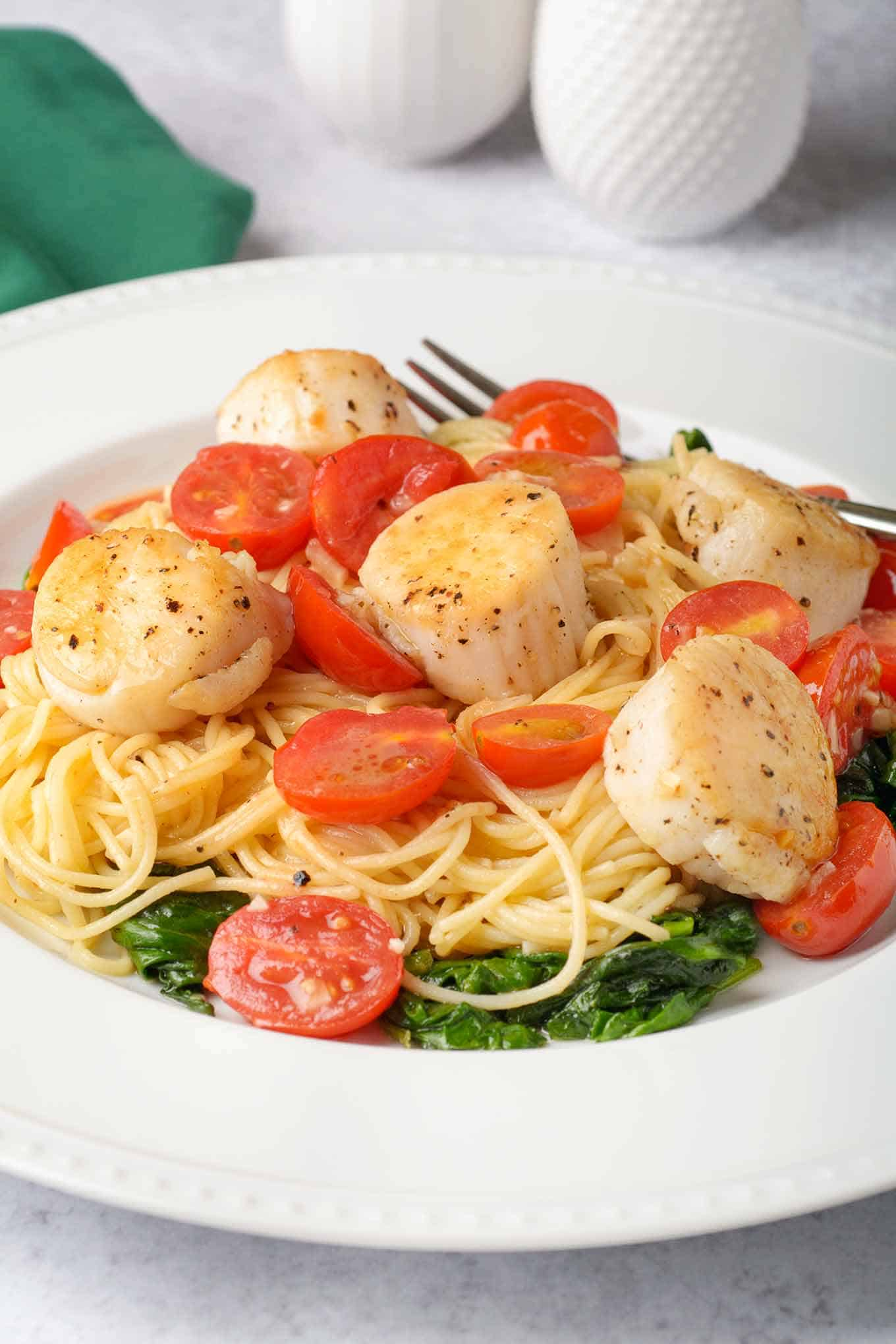 A serving of pasta, seared scallops and grape tomatoes tossed with white wine butter and served over a bed of sautéed spinach.