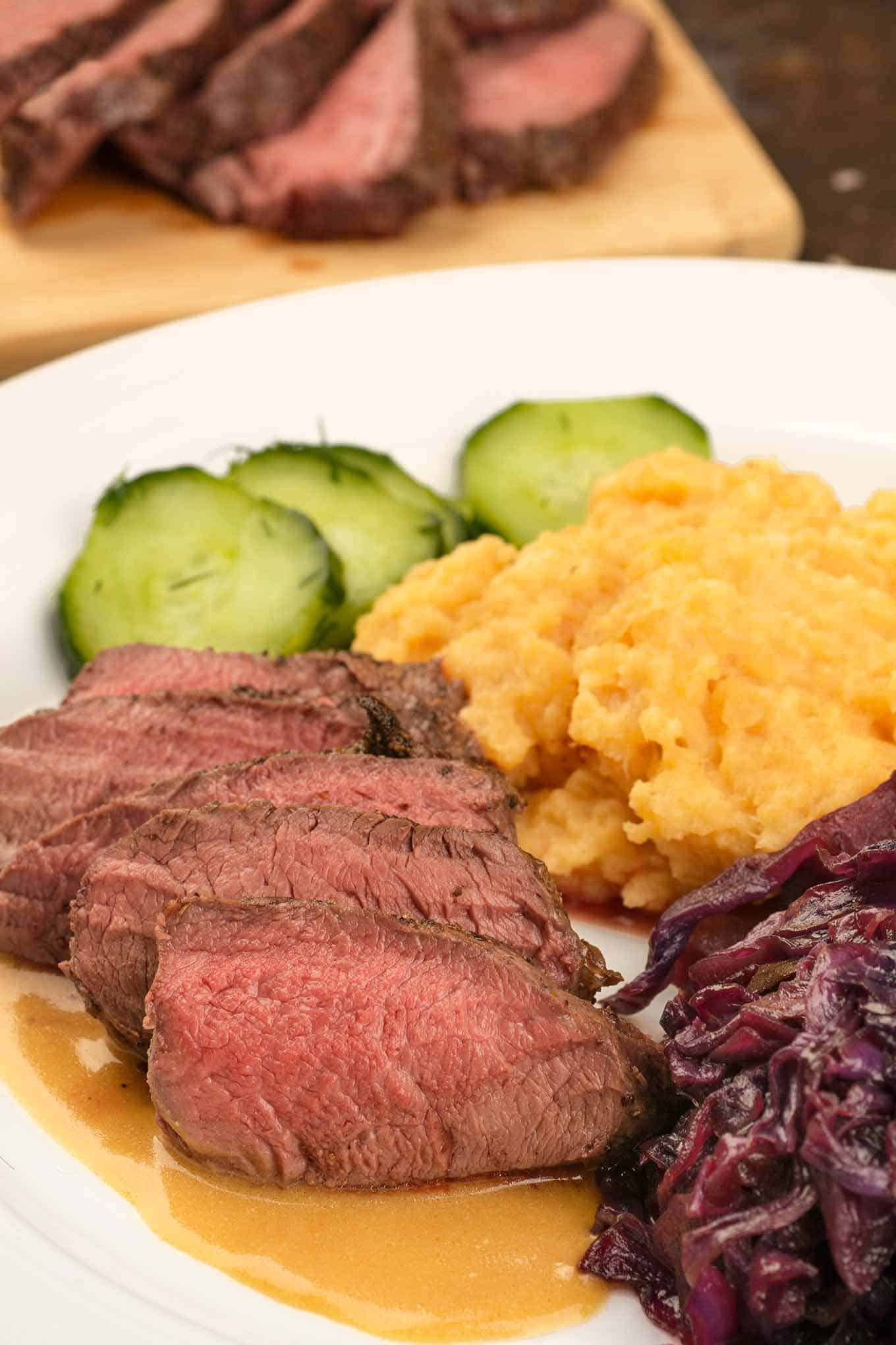 Sliced venison tenderloin on a plate with side dishes and sauce