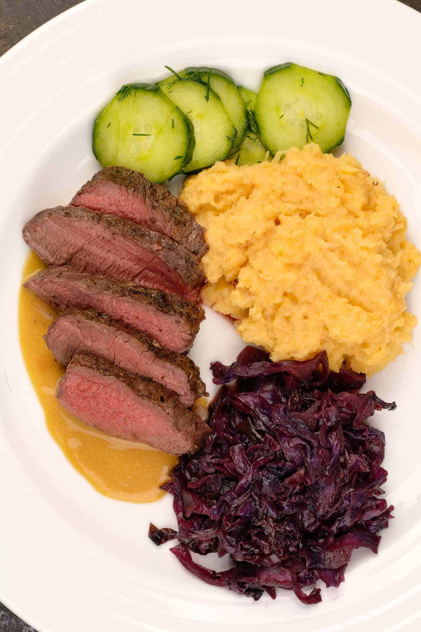 Slices of roasted venison tenderloin on a plate with Scandinavian-style side dishes