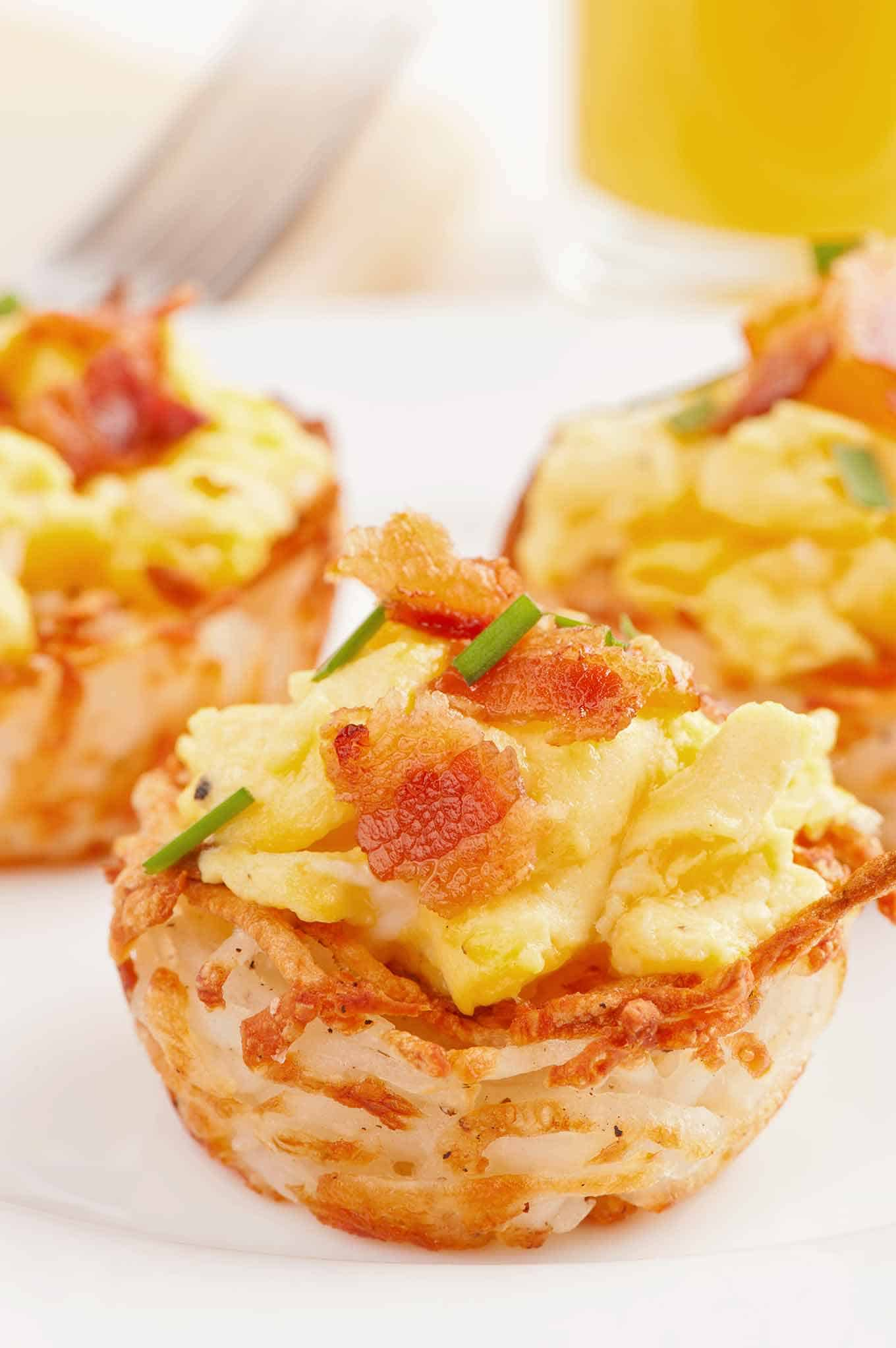 Scrambled eggs inside hash browned potato cup topped with bacon and garnished with chives.