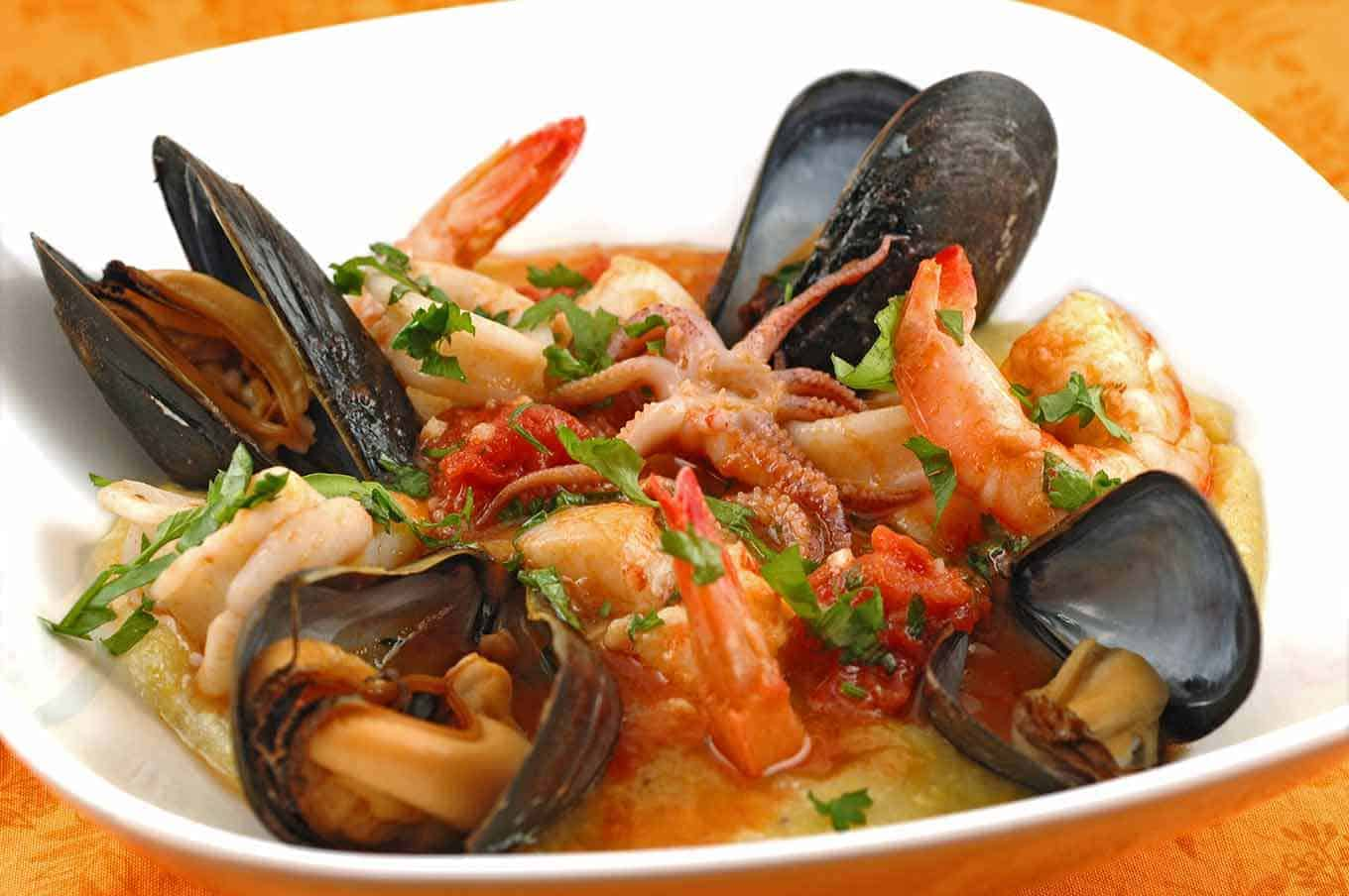 A shallow bowl of soft polenta topped with shrimp, scallops, mussels, and squid cooked in a light, tomato butter sauce.