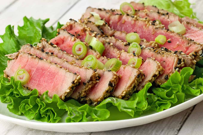Seared rare tuna steak on a platter of green leaf lettuce.