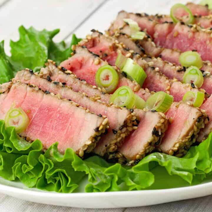 Sliced sesame-crusted, rare tuna on a bed of lettuce.
