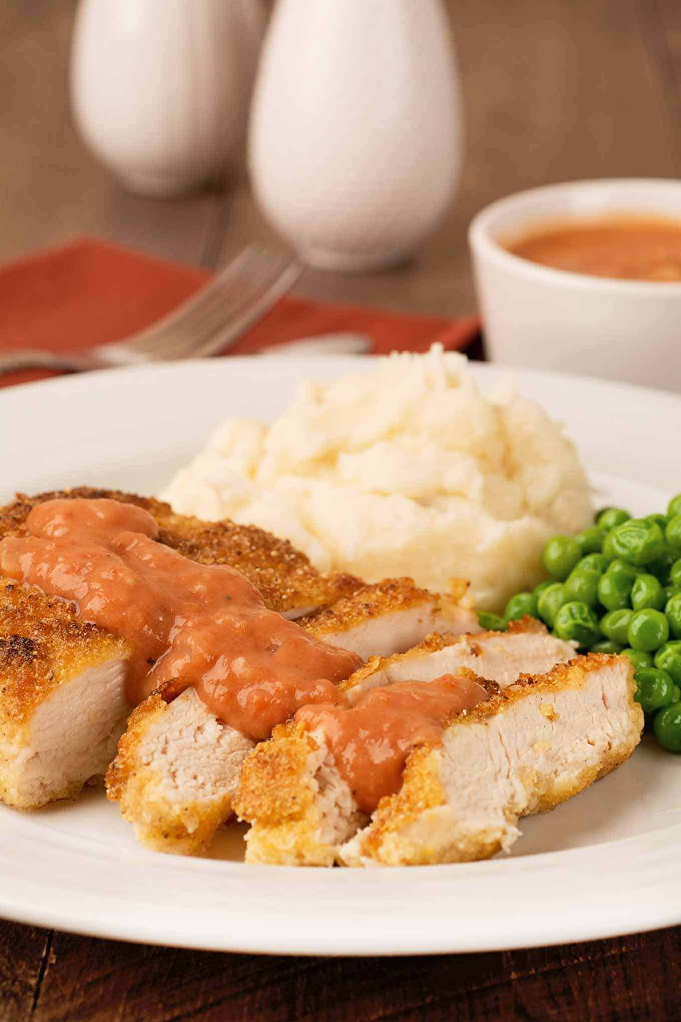 Plate with shallow-fried chicken breast, sliced and topped with Southern tomato gravy.