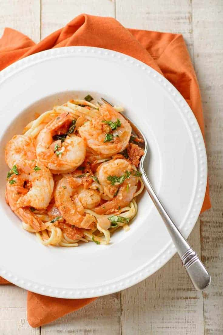 Shrimp Fra Diavolo is an Italian-American dish of pasta tossed with tender shrimp and a light, spicy tomato sauce flavored with red pepper flakes and garlic. #shrimp #linguine #shrimpfradiavolo