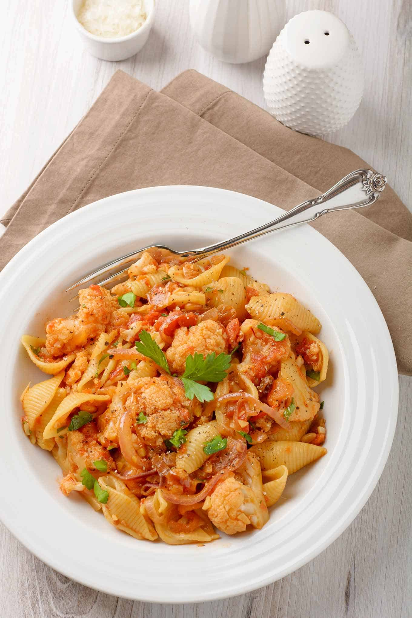 A bowl of pasta shells tossed with Sicilian tomato and cauliflower sauce, and a cloth napkin and grated cheese in the background.