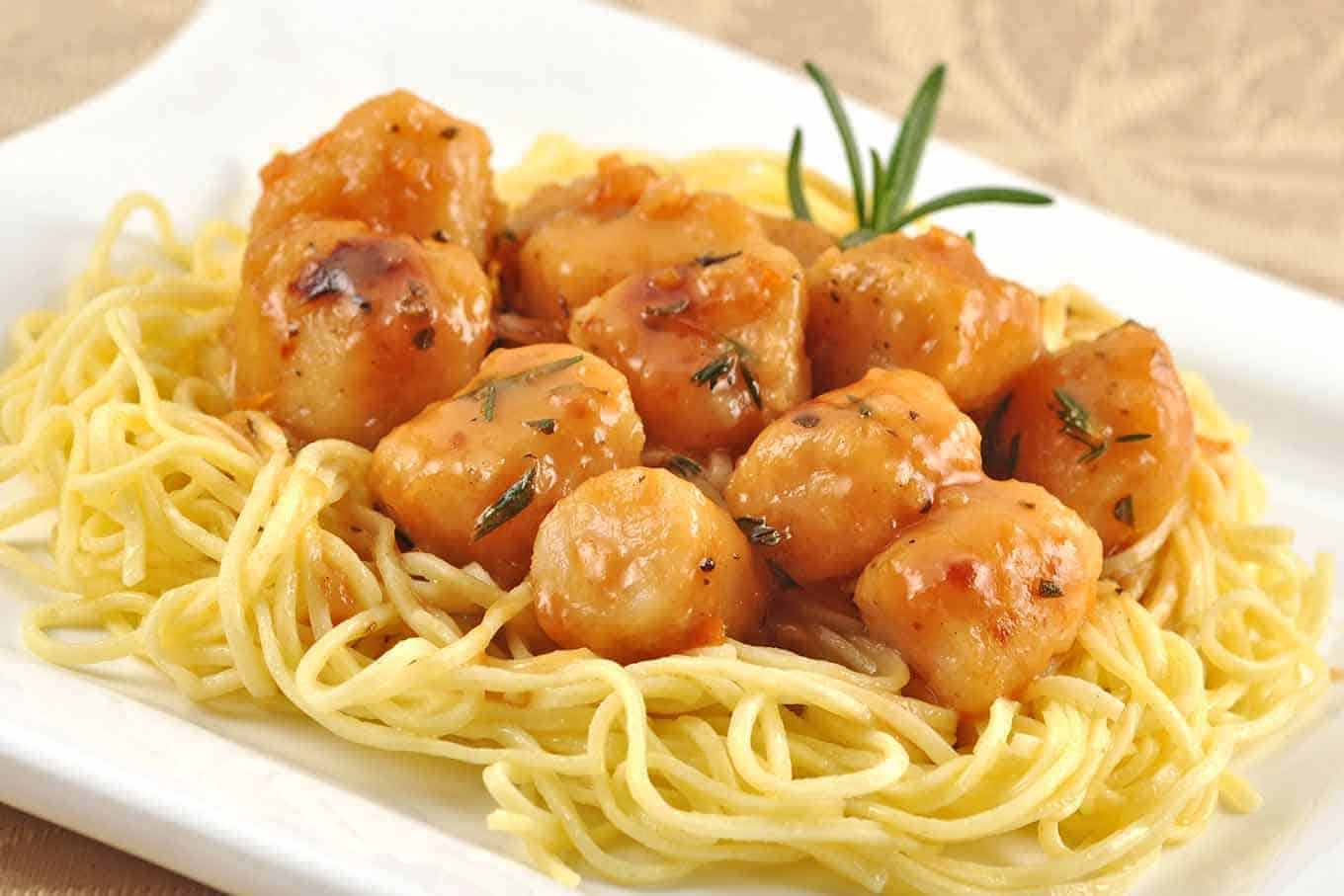 Sicilian-style citrus scallops served over spaghetti on a serving plate