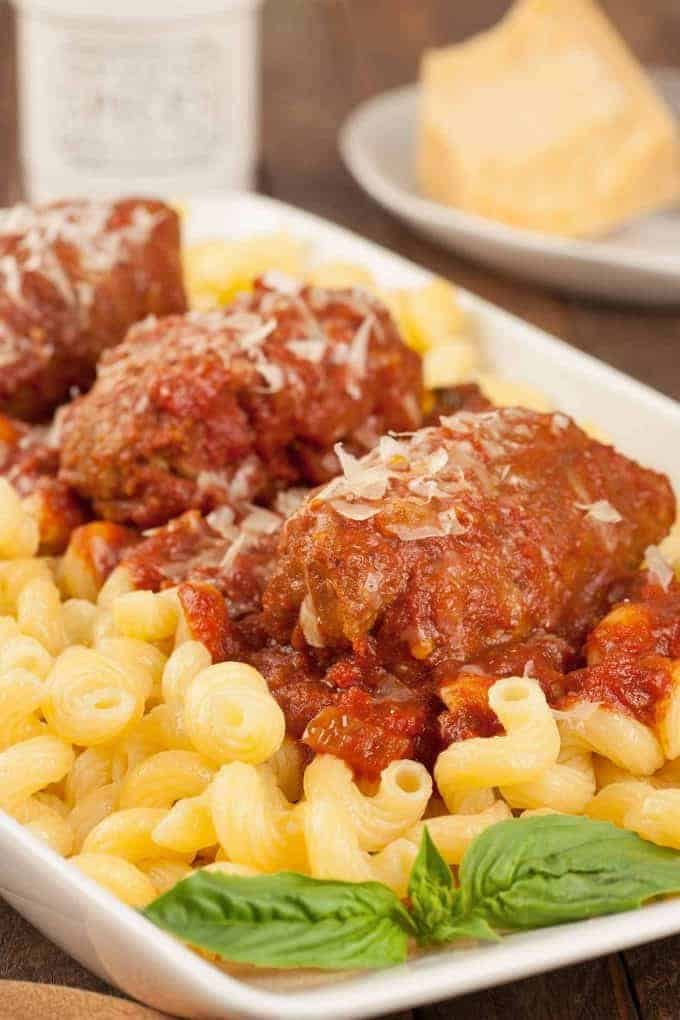 Slow cooker beef braciole served over pasta on a serving plate