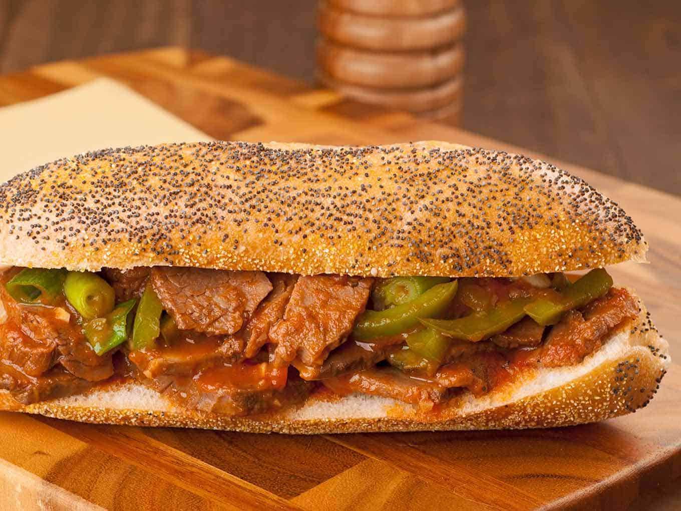 Sandwich of sliced brisket, sautéed green peppers, scallions and barbecue sauce on a poppy seed hoagie roll