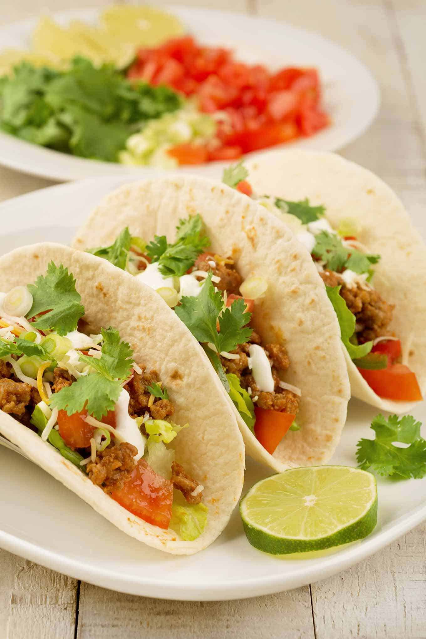 Three ground turkey tacos on a plate with a lime wheel.