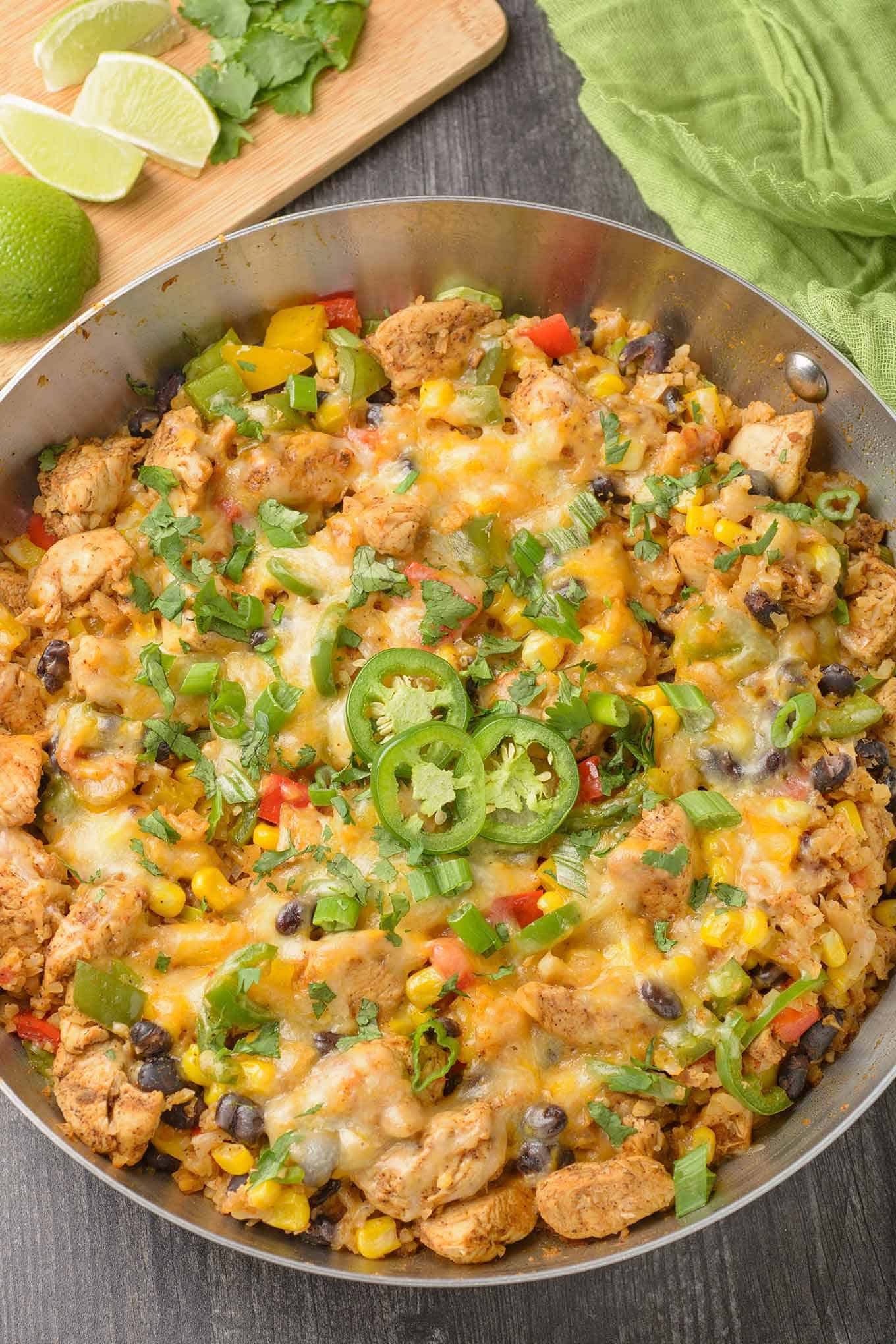 A frying pan filled with chicken, riced cauliflower, black beans, corn, melted cheese, green onions and cilantro.