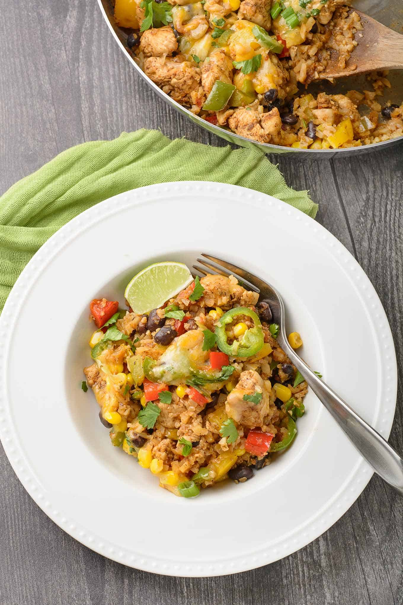 A single serving of chicken and cauliflower rice plated in a shallow bowl with the serving skillet in the background.
