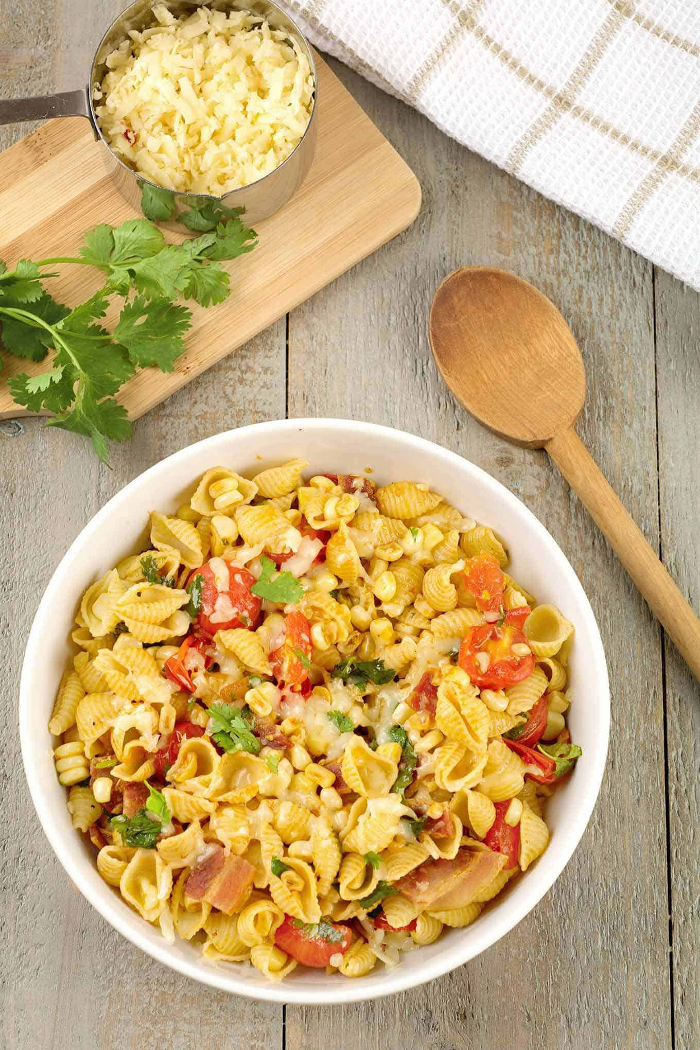 Serving bowl of pasta, bacon, corn, fresh tomatoes, and cheese surrounded by cilantro, grated cheese and wooden spoon.