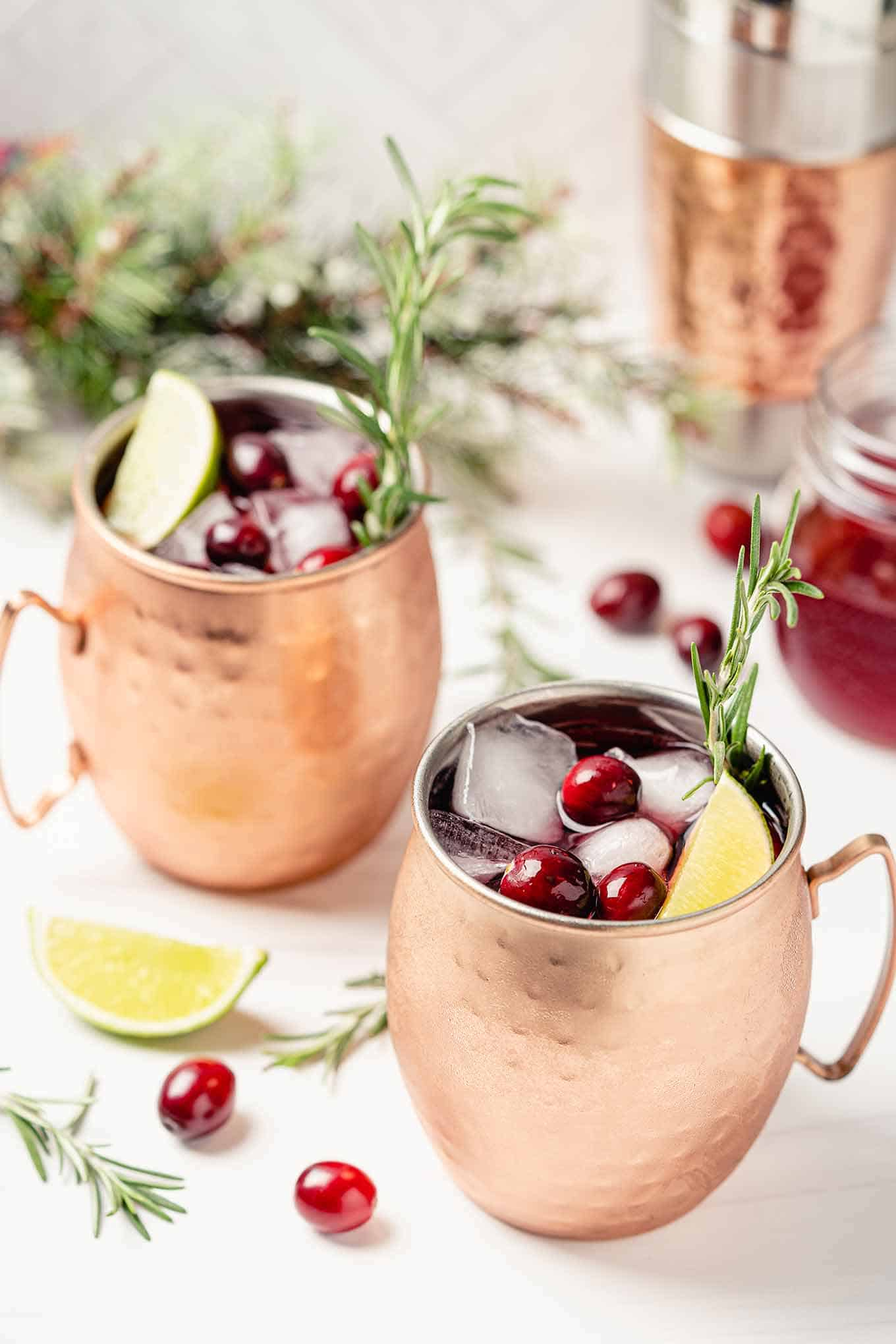 Two copper mugs of cranberry Moscow mule garnished with fresh cranberries, lime, and rosemary.