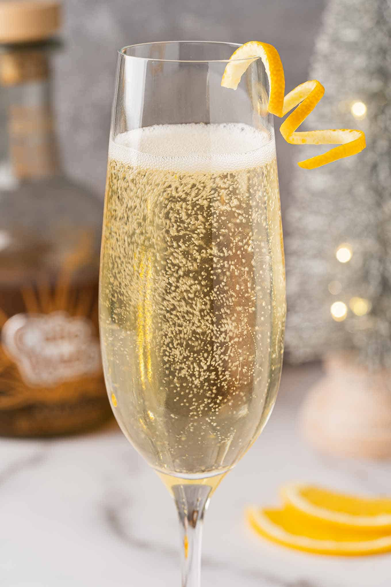 Sparkling wine cocktail in a champagne flute garnished with an orange twist, orange slices.