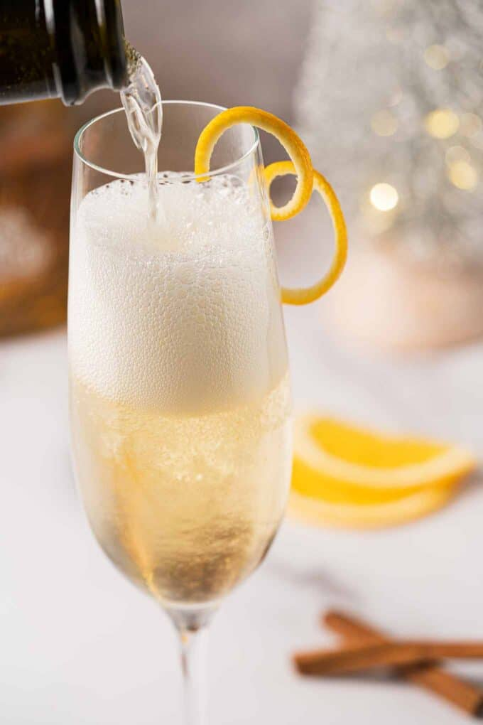 Champagne being poured into a flute glass with tequila and spiced orange syrup