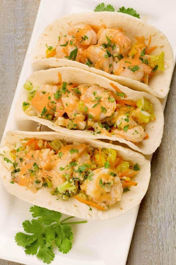 Topped with spicy sriracha mayo, these easy Asian shrimp tacos are filled with stir-fried garlic-ginger shrimp, scallions, cilantro and a simple Napa cabbage slaw.
