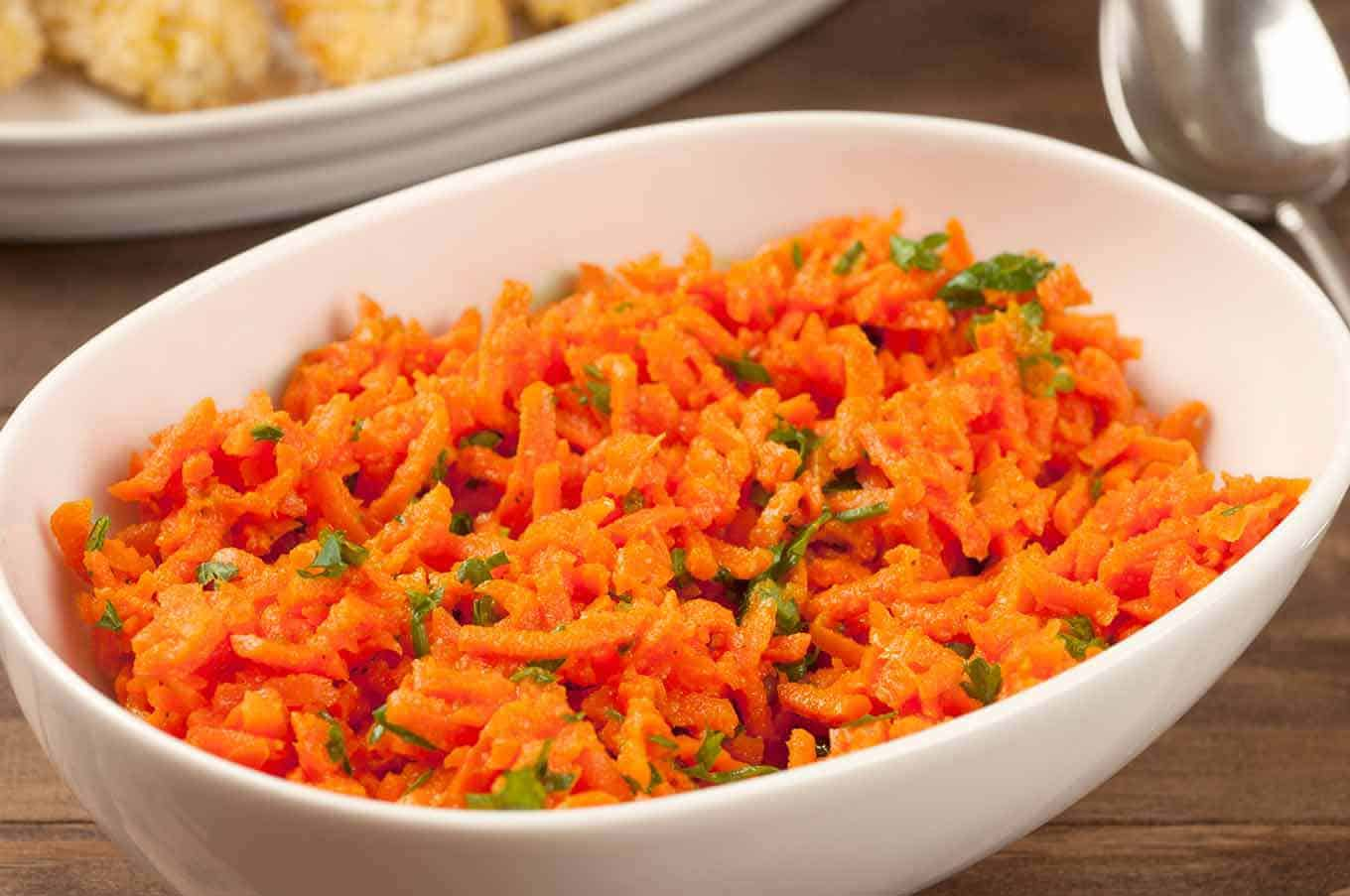 A serving bowl of carrot salad garnished with parsley.