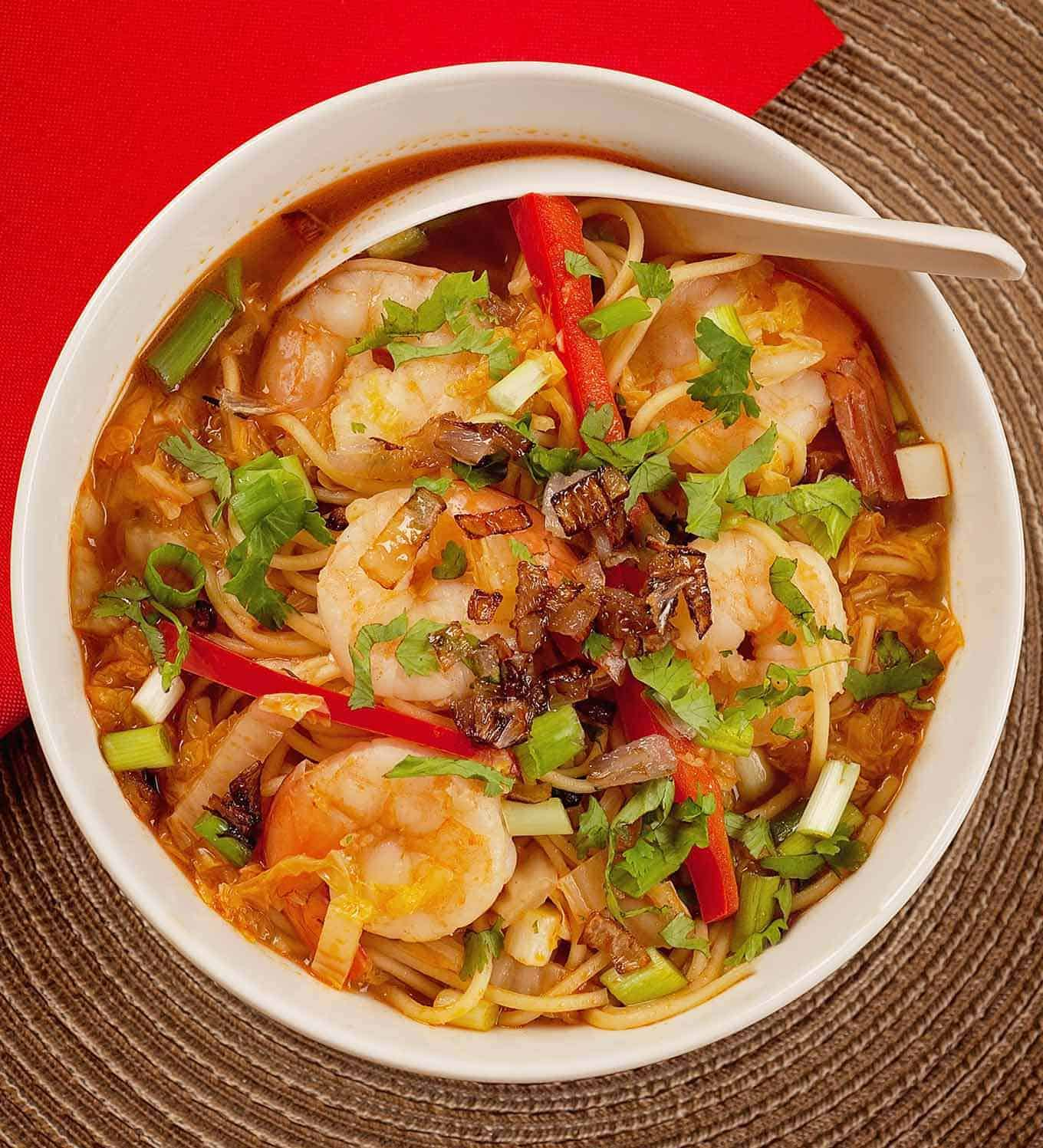 Bowl filled with ramen noodles, shrimp, Napa cabbage, red bell pepper, and garnished with scallions and cilantro.
