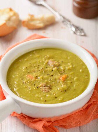 Single serving of split pea soup in white crock.
