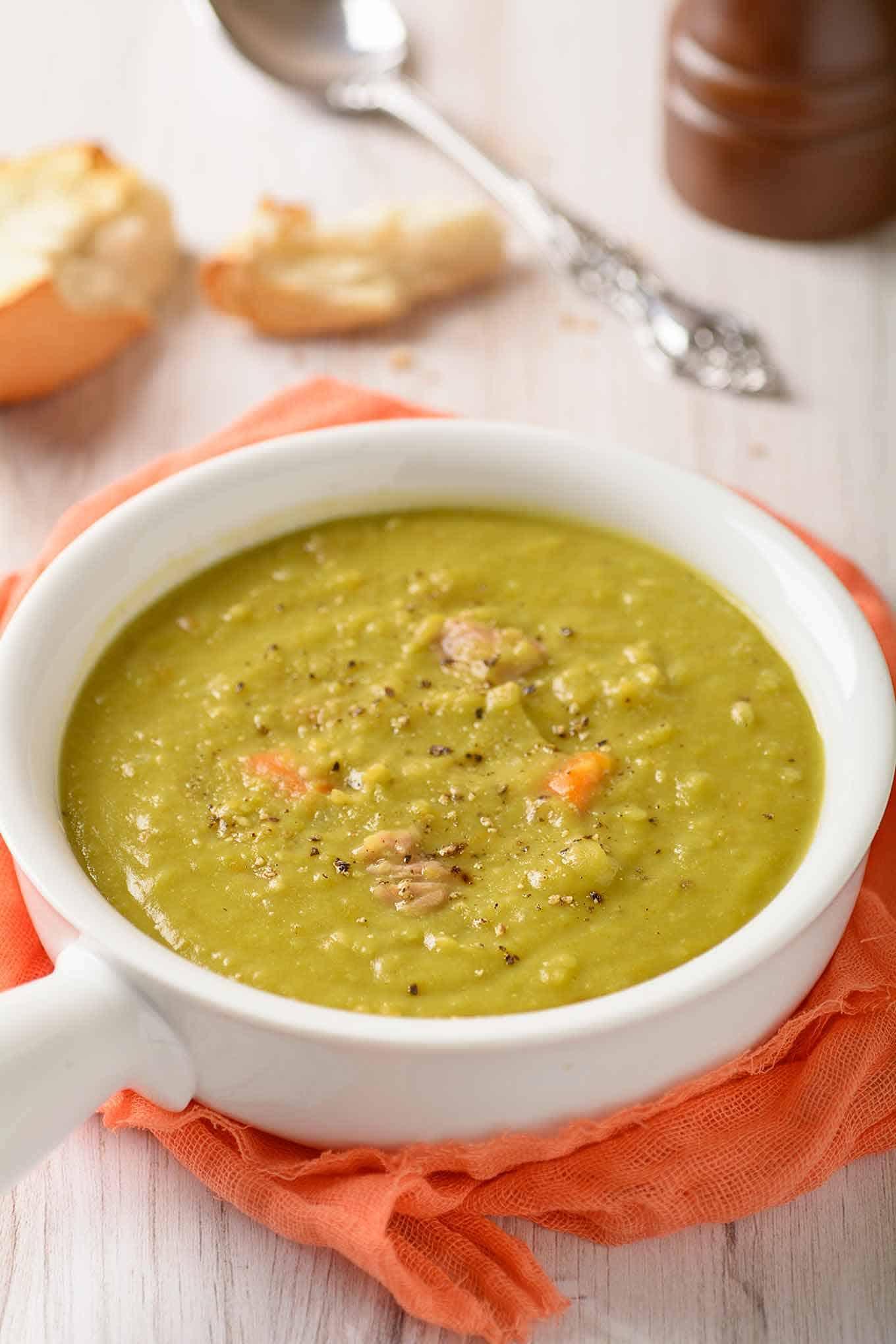 Single serving of split pea soup in white ceramic crock.