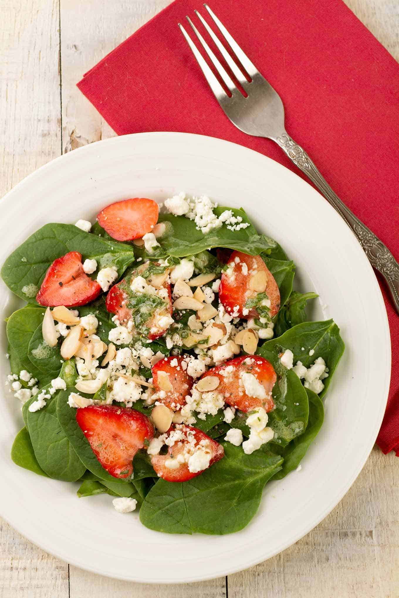 Single serving of spinach and strawberry salad topped with sliced almonds and crumbled goat cheese.