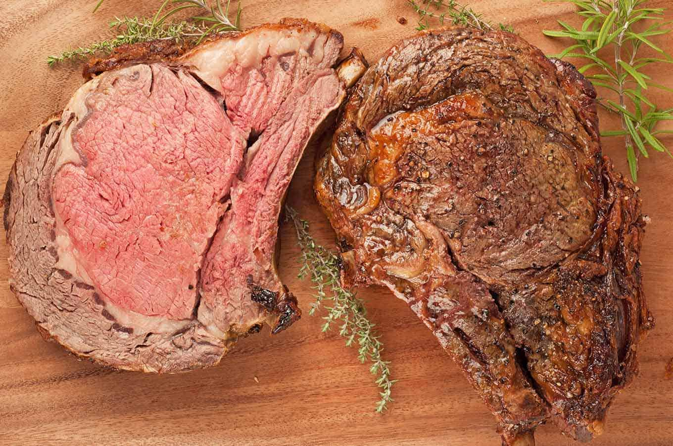 Prime rib standing beef roast sliced with herbs.