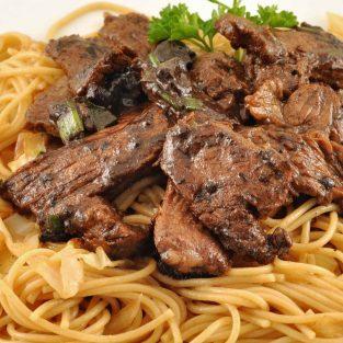 Stir-fried steak with black garlic sauce over noodles