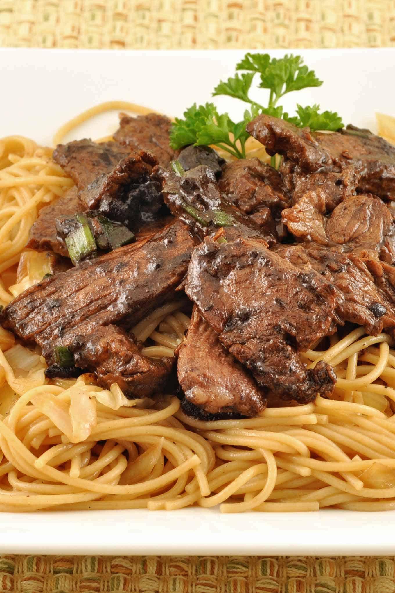 Stir-fried steak with black garlic sauce served over noodles