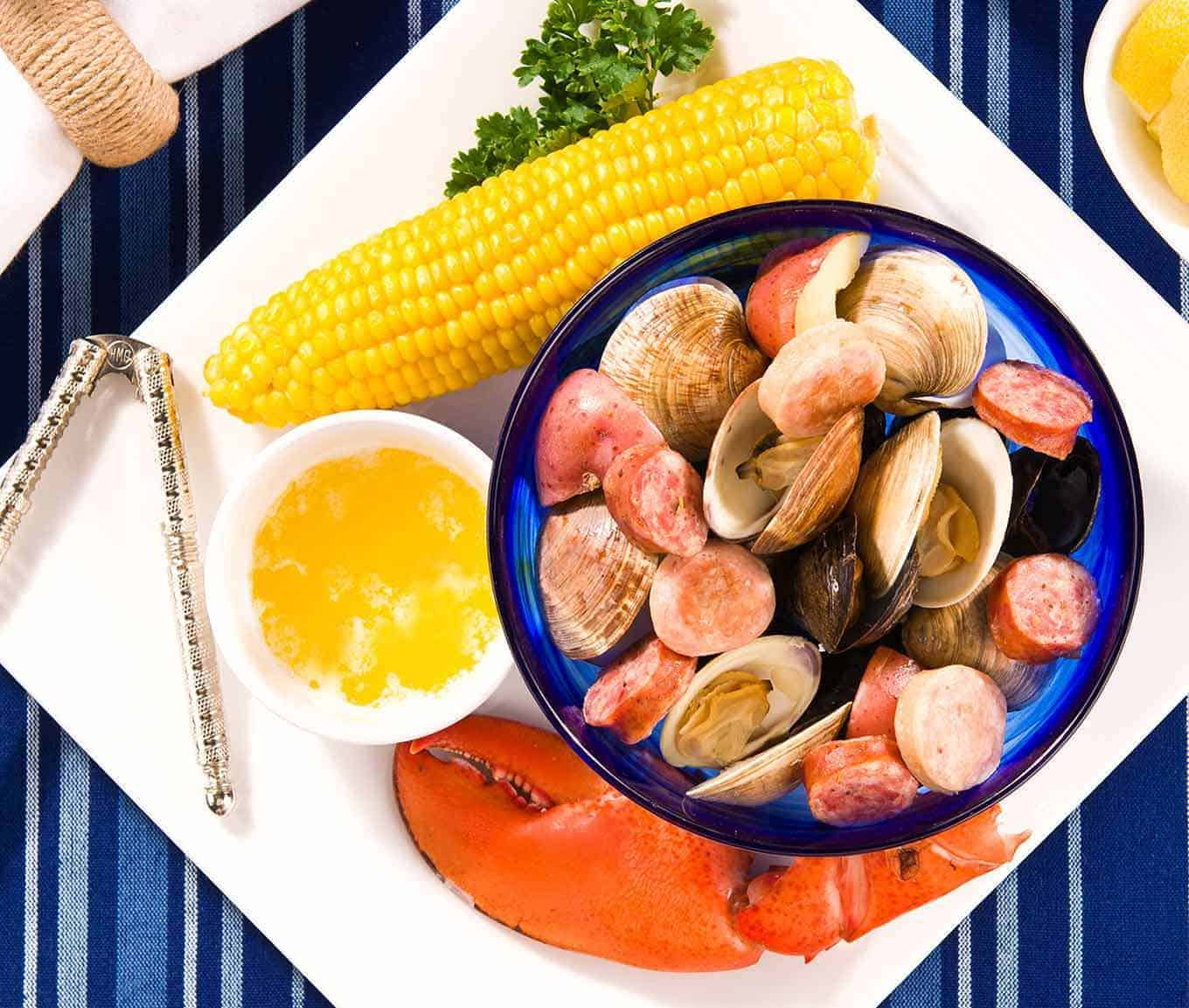 Plate containing lobster claw, ear of corn, bowl of melted butter, nutcracker, and bowl of steamed clams, mussels, sausage, and potatoes.
