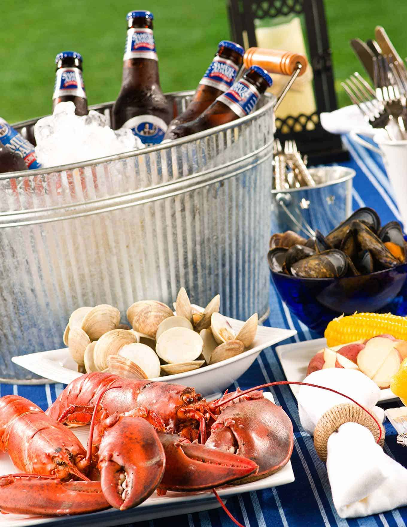 Table filled with with lobsters, clams, mussels, potatoes, corn, utensils, and an ice-filled bucket with cold bottles of beer.
