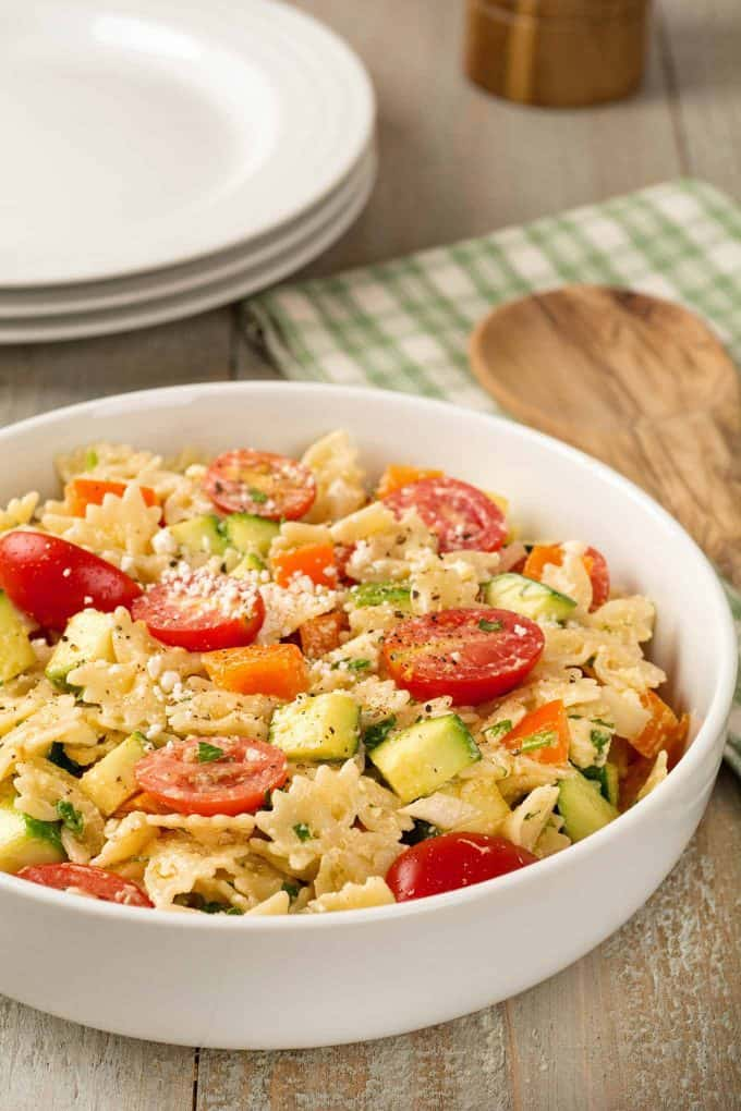 Bowl of pasta salad with zucchini, tomatoes, bell pepper and feta cheese.