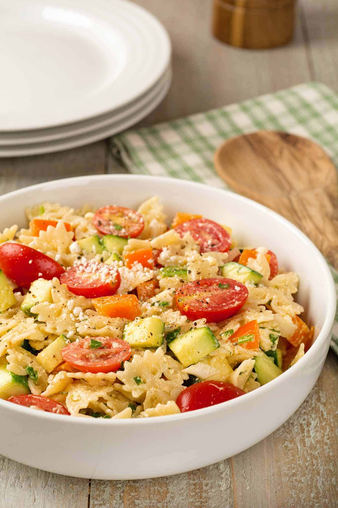 Bowl of pasta salad made with zucchini, tomatoes, bell pepper and feta cheese.