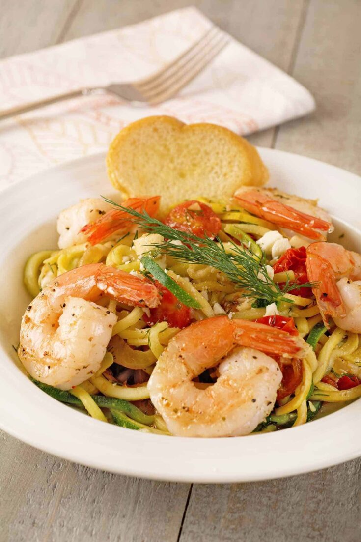A light, flavorful, one-dish meal made with spiralized noodles made from zucchini and yellow squash, sautéed shrimp, cherry tomatoes, fresh dill and feta cheese. #zoodles #zucchininoodles #shrimp