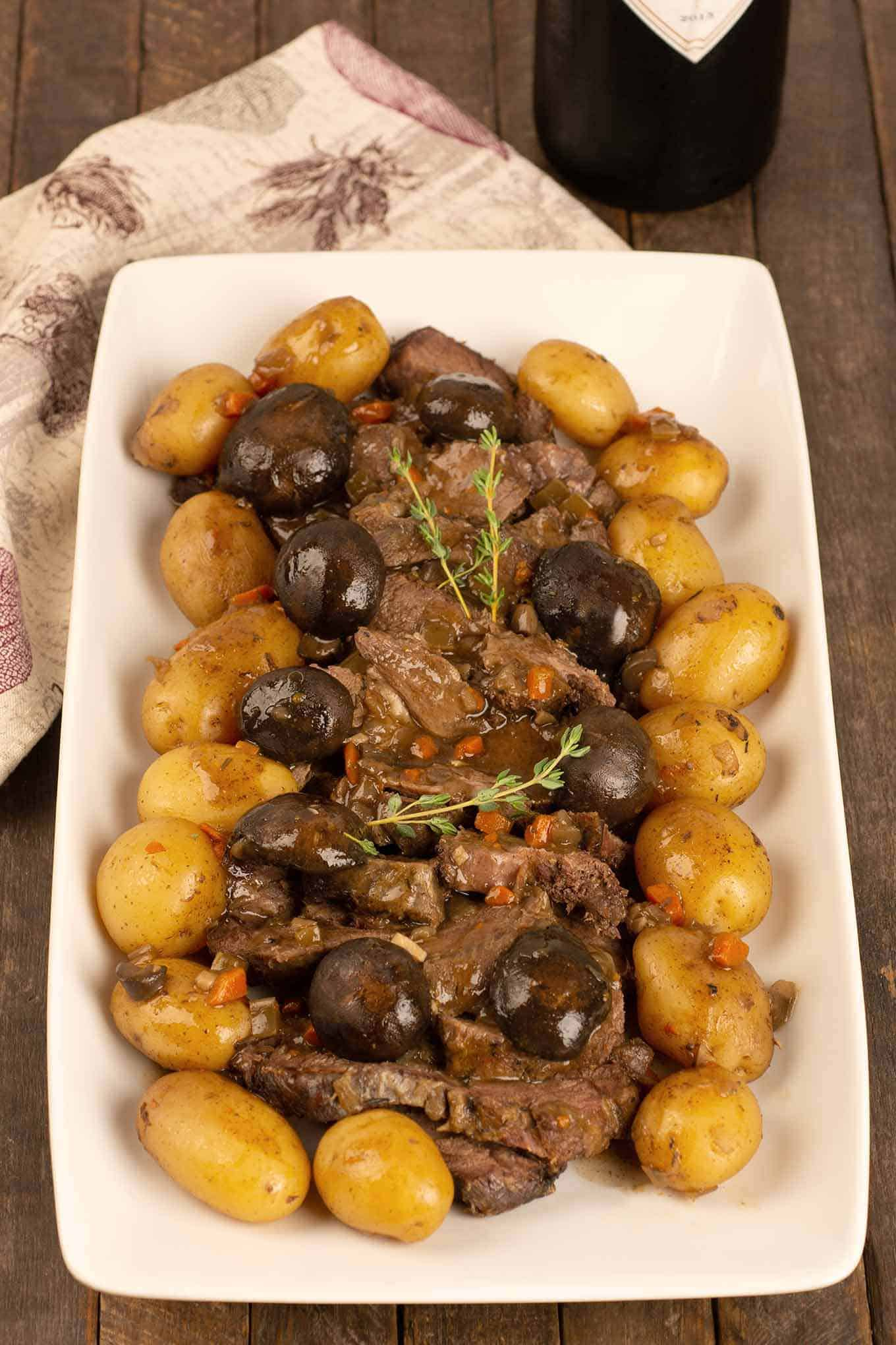 A serving platter with sliced pot roast, mushrooms and baby potatoes garnished with fresh thyme sprigs.