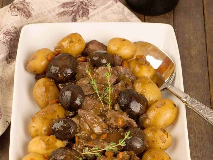 Boneless chuck roast, baby potatoes, mushrooms, red wine and fresh thyme combine to make this slow-cooker pot roast recipe a company-worthy Sunday meal. #potroast #slowcooker #beef