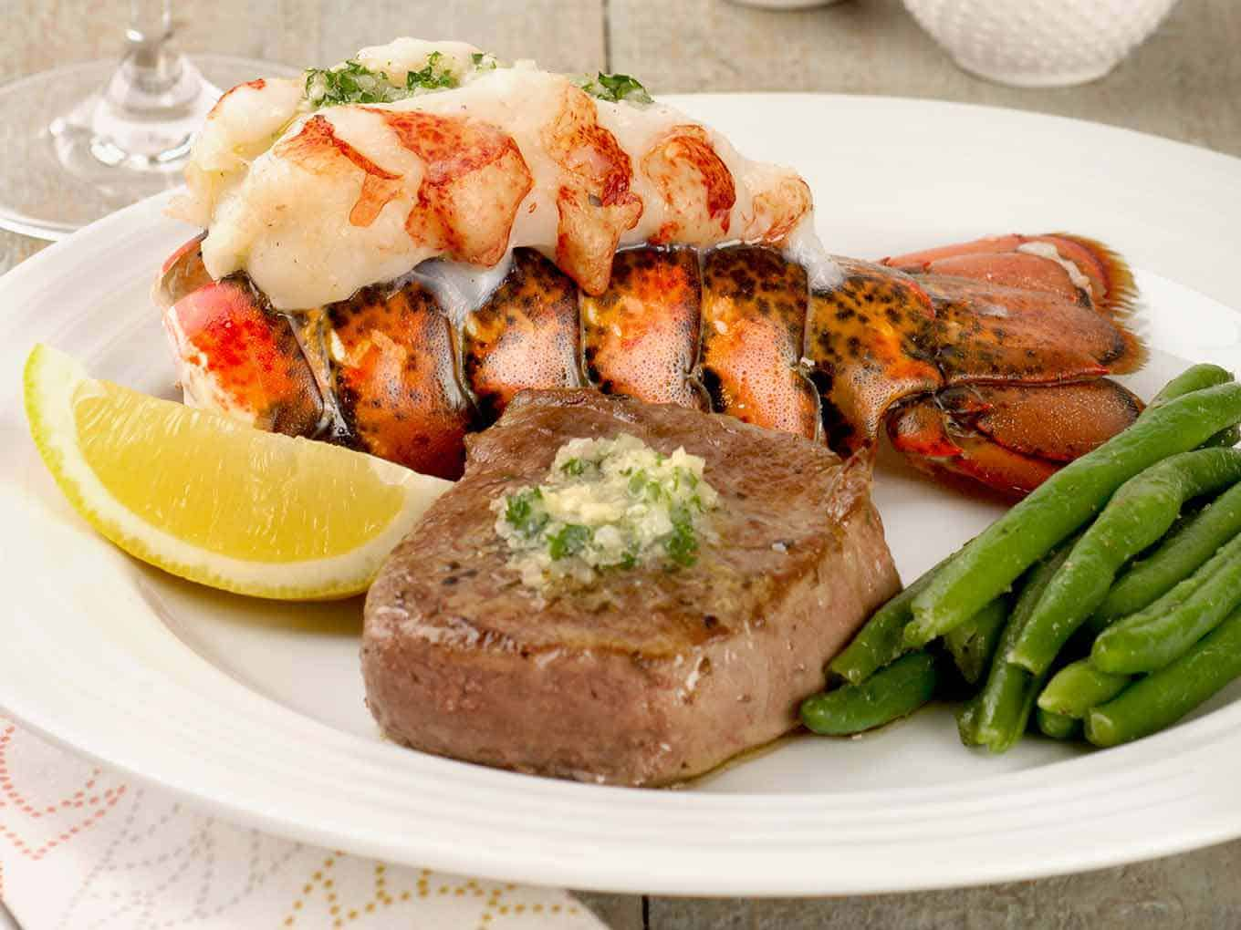 Single serving of filet mignon and lobster tail topped with compound butter