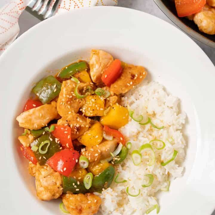 Sweet and sour chicken plated with steamed white rice