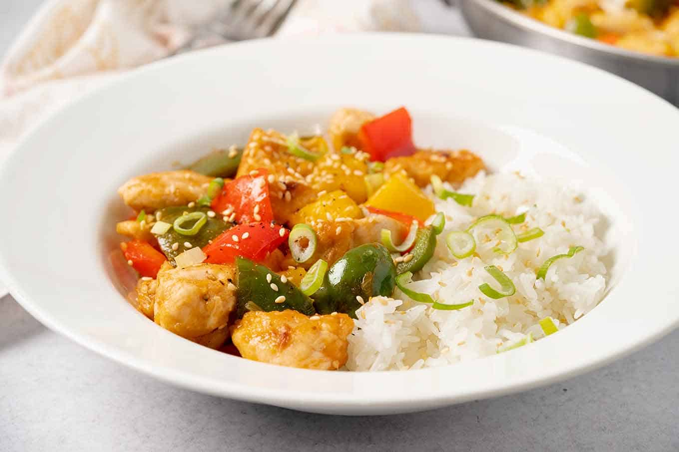 A single serving of sweet and sour chicken with white rice on the side.
