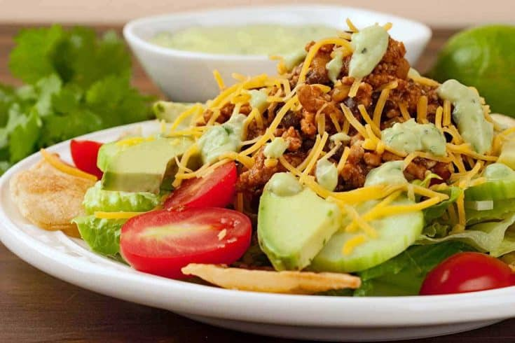 Made with taco-style spices, ground beef and a creamy avocado dressing, this tasty taco salad is a hearty one-dish meal. #maindish #dinner #salad #groundbeef #taco