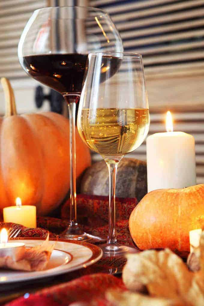 Two glasses of wine, one red, one white on a table decorated with pumpkins and candles.