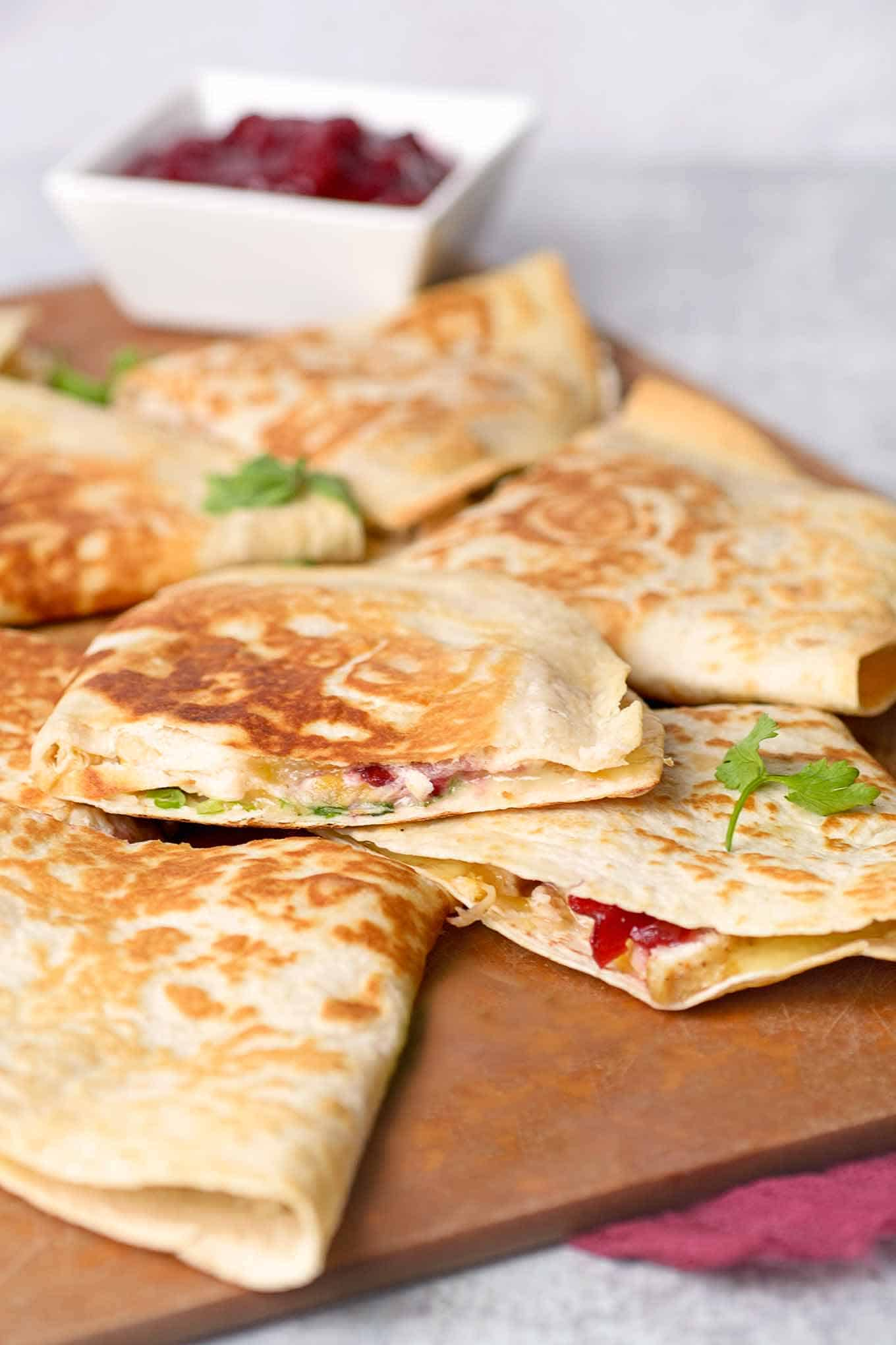 Wedges of turkey quesadillas on a cutting board with a dish of cranberry sauce in the background.