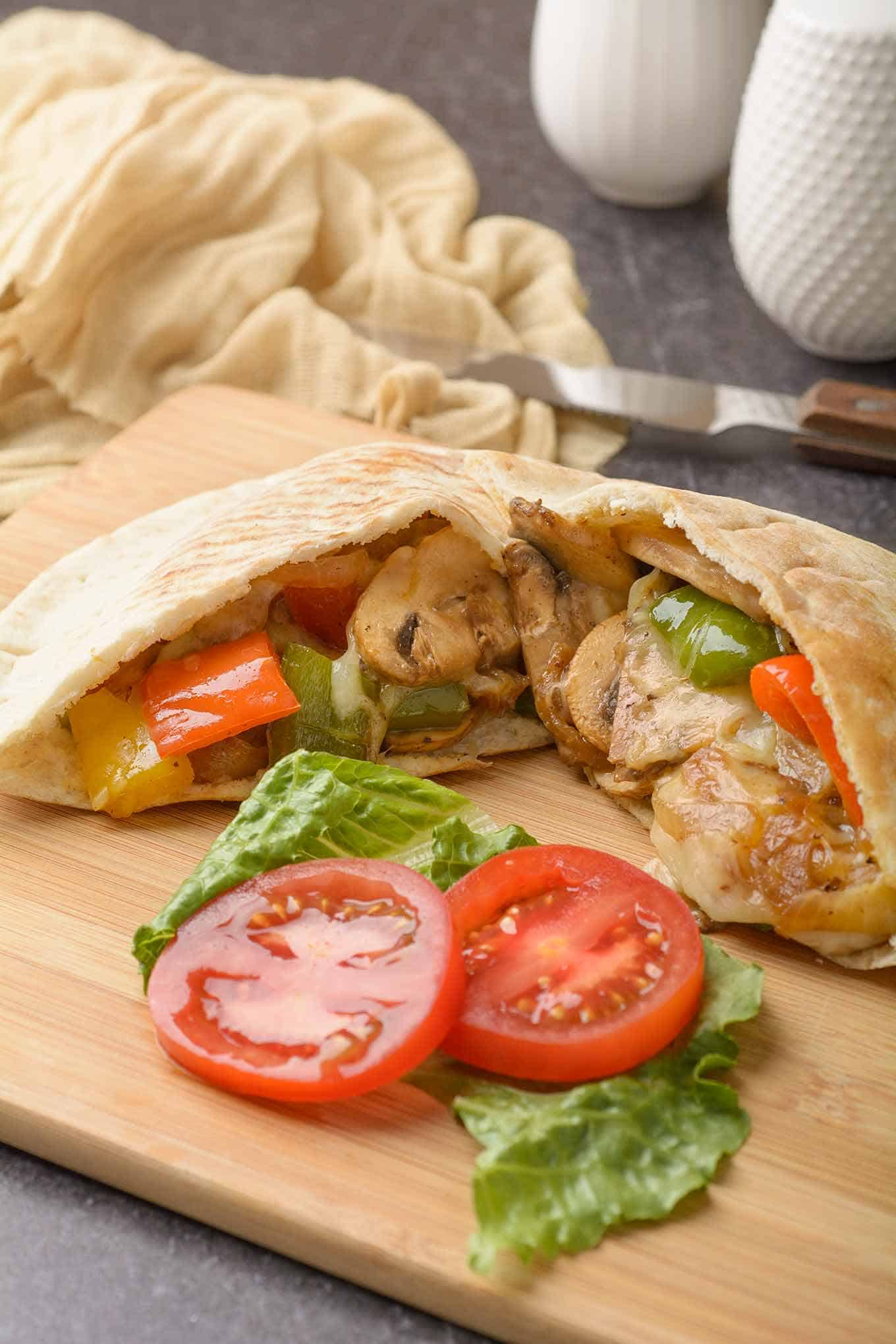 Pepper and mushroom pita sandwich on cutting board with fresh lettuce and tomato
