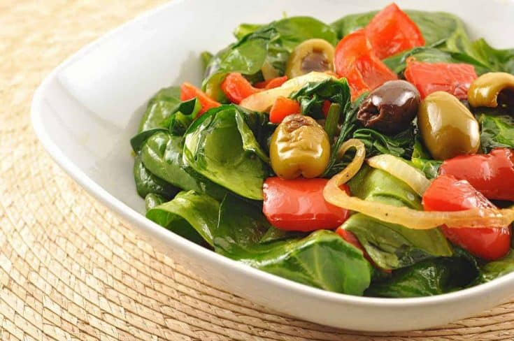 This is a simple, flavorful salad made by roasting a combination of olives and red peppers and tossing them, straight from the oven with fresh spinach. #olivesalad #spinachsalad